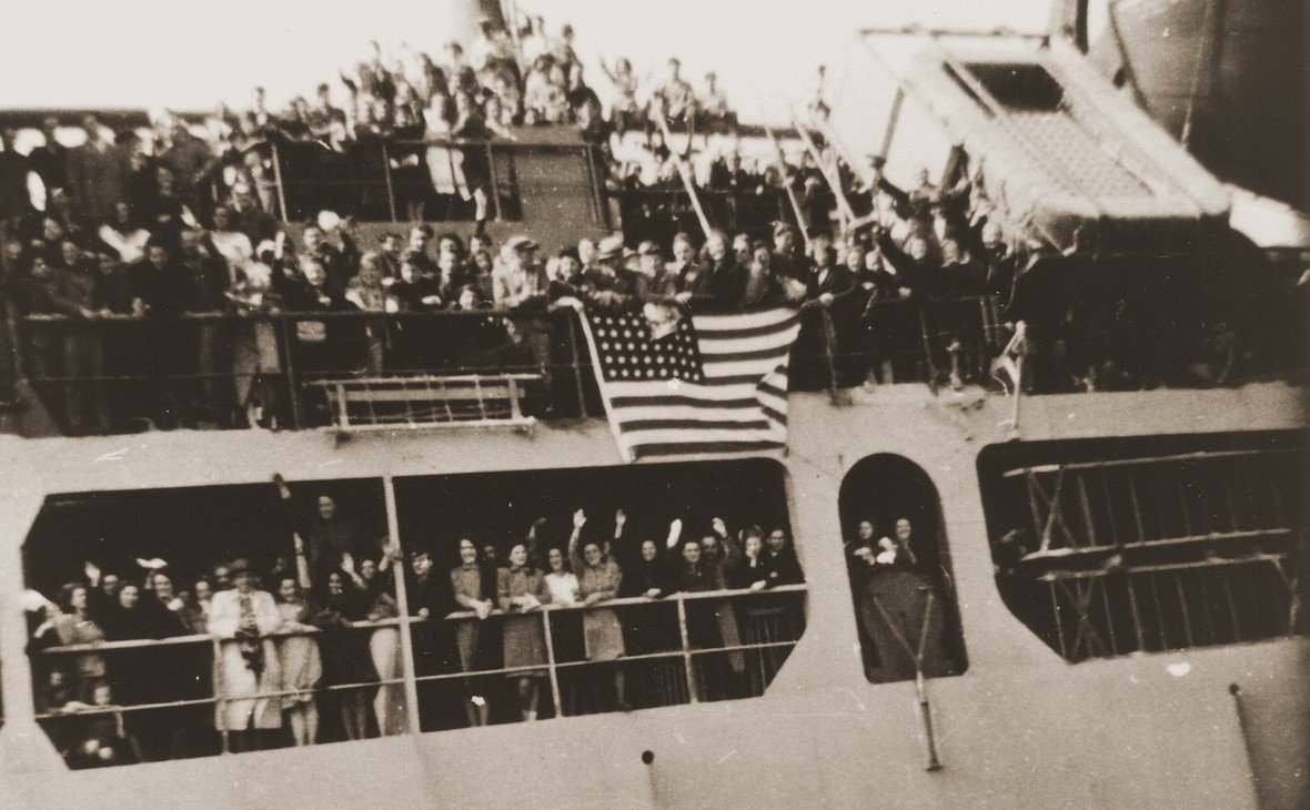 grainy b&w photo of a crowd waving from aboard the dual decks of a metal ship